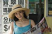 肖像,年轻,女人,读,报纸,公交车站,微笑
