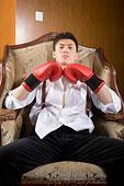 一個男人戴著拳擊手套坐在椅子上看著鏡頭