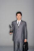 一名穿著職業裝的先生拎著公文包舉起獎杯