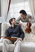 兩位先生拿著小提琴對著鏡頭微笑