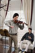 一位先生在教另一位先生拉小提琴