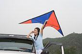 一對年輕的女孩開著越野車在郊外放風箏