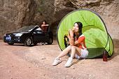 一對年輕人開著奧迪車在郊外的山洞前的帳蓬邊休息