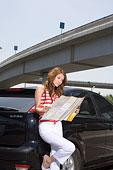 一个穿着休闲装的年轻女人拿着地图站在车边