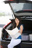 一个穿着休闲装的年轻女人趴在车上看地图
