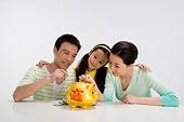 一家三口共同往存錢罐裏存錢