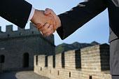 两位中外商务人士在长城上握手特写