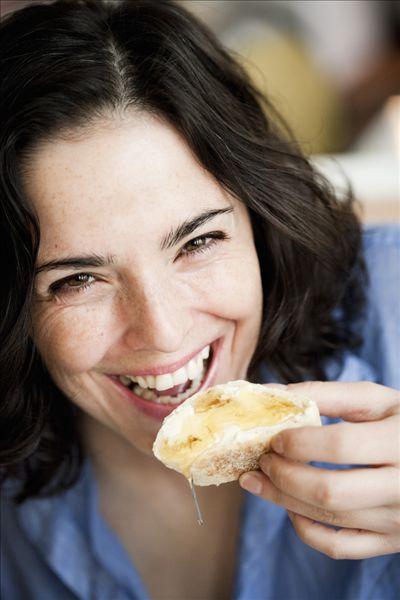 女人吃面包和蜂蜜_全景图片