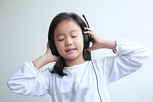 带着耳机闭眼听音乐的可爱女孩