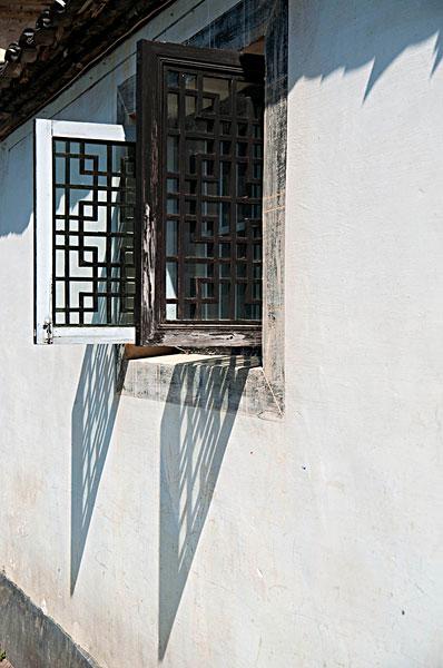 白色的墙和开着的黑色木窗