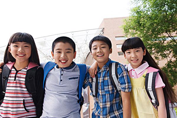 可爱的小学生在校园里搂着肩膀站着