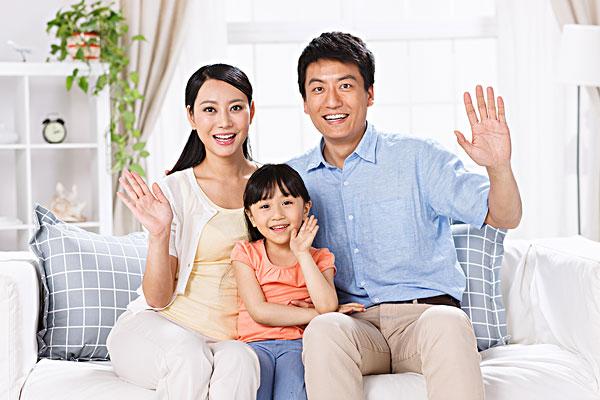幸福的一家三口在客厅的沙发上坐着