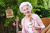 一个老年女人拿着皮影偶