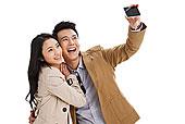 青年情侣拿着手机在自拍