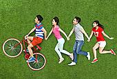 年轻男女手牵手在草地上奔跑