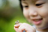 青蛙坐在女孩的手指