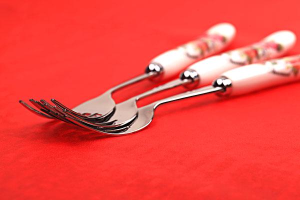三把银色带红色花纹的叉子摞在一起