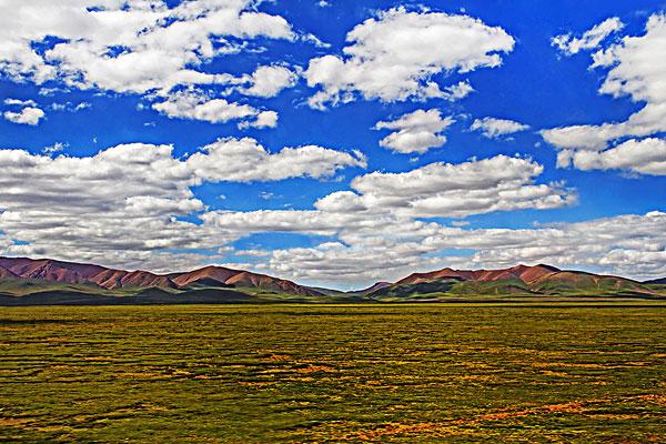 中国西藏高原蓝天白云下的草原和山脉