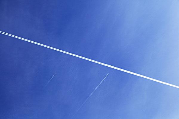 飞机喷气形成的白线在蓝天下划过